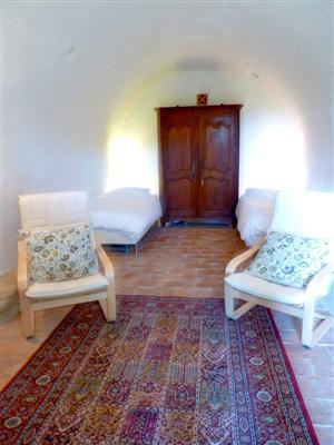 From the living area, you wind down the stairs into the lower level of the house. Along the way, you pass the original stone wall of the house.  Here you enter Bedroom 3.  This is the original caved room of the house dating back to the birth of the village.